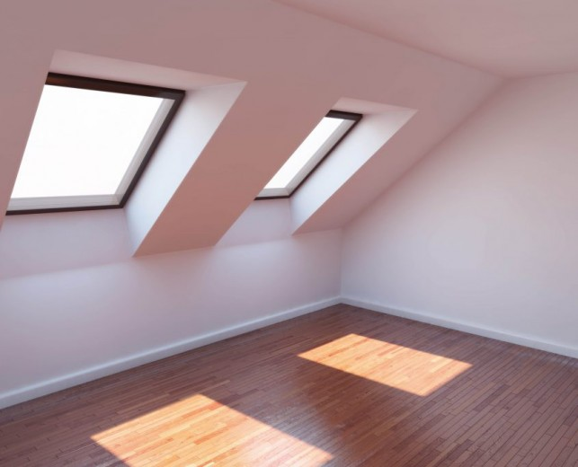 An image of a modern loft conversion with laminate flooring and two windows.