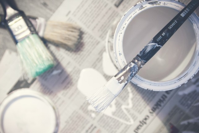 An image of a open paint pot on newspaper.