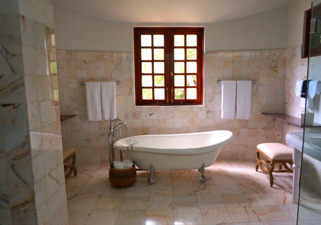 An image of a traditional, Victorian style bathroom with a freestanding roll top bath.