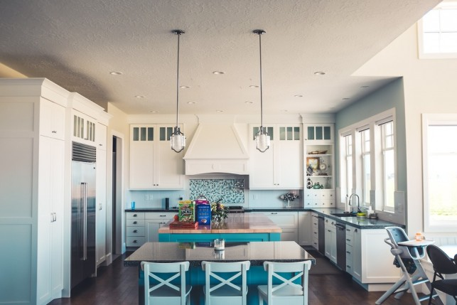 An image of modern country style kitchen, with hard wooen flooring and pendant lighting over a kitchen island.