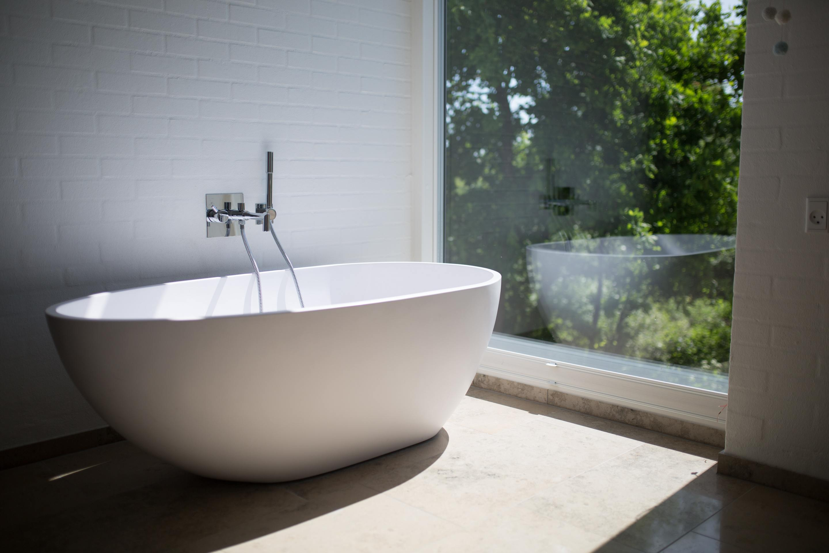 An image of a curved edge. free-standing, white bath with silver taps, in a bathroom, next to a large window with greenery outside.