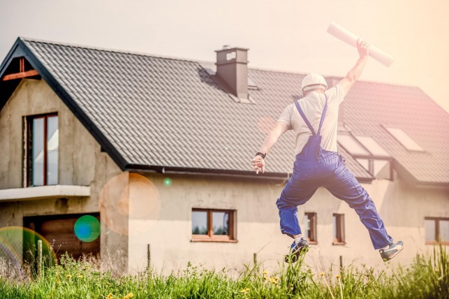 An image of a homeowner, jumping for joy, with planning permission documents in his hands, and a house in the background.